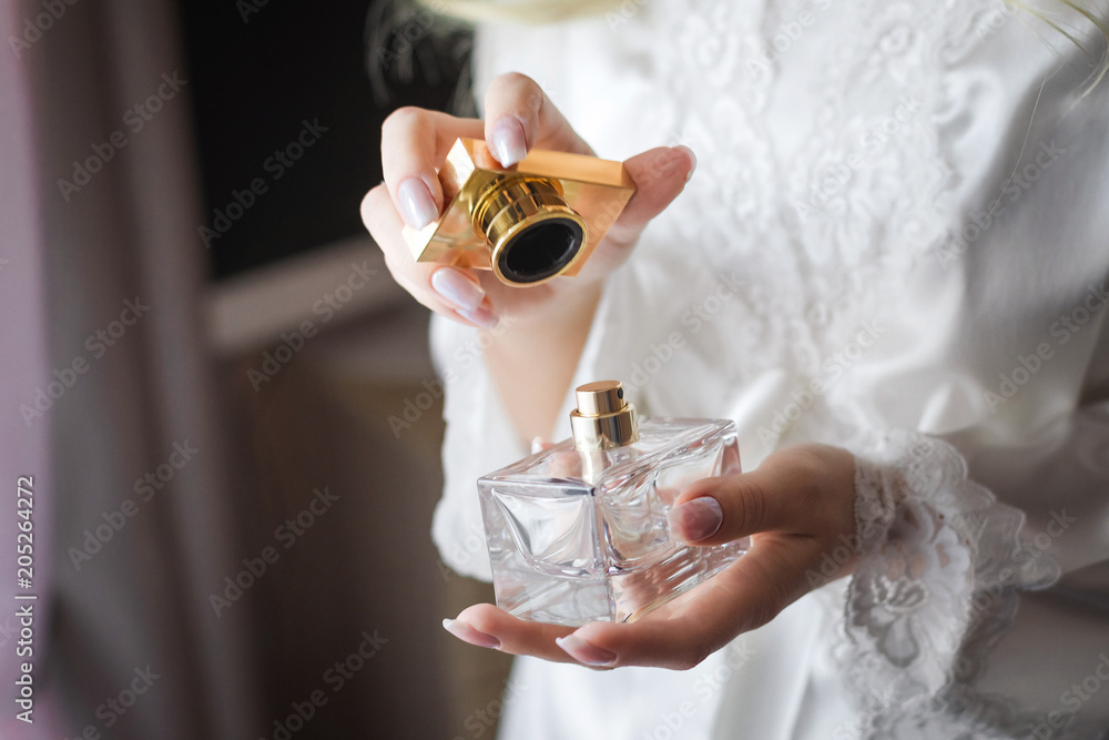Fototapety, obrazy: Close up shoot of a luxury fragrant perfume flacon in manicured hands of elegant bride wearing white dressing gown