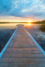 Vertical Photo Of A Beautiful Landscape - A Long Wooden Pier And A Setting Sun Over A Picturesque Lake