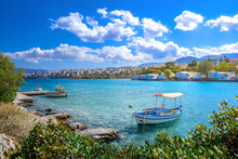 Small Natural Harbor With Anchored Fishing Boats With The Beautiful Town Of Agios Nikolaos At The Background, Crete, Greece.