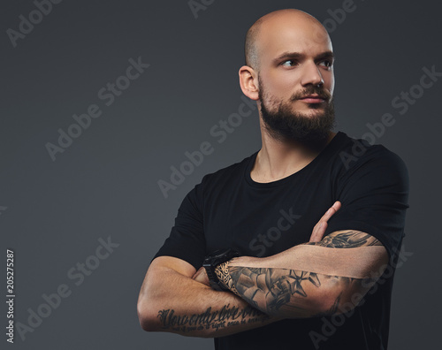 Close-up portrait of a handsome bearded athlete in a black t-shirt, posing with crossed arms in a studio. Wall mural