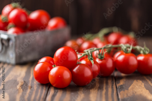 Small red cherry tomatoes on rustic background. Cherry tomatoes on the vine