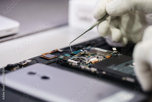 Work with a microscope. Microelectronics device. Close-up hands of a service worker repairing modern smartphone. Repair and service concept.
