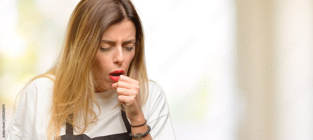 Fototapeta Shop owner woman wearing apron sick and coughing, suffering asthma or bronchitis, medicine concept