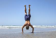 Muscular Man Doing Handstand On Beach