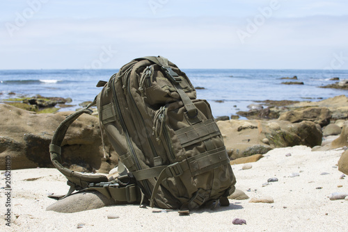 Adventure backpack on sand with ocean in background