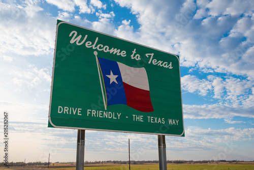 Fotografia, Obraz Welcome to Texas road sign in front of cloudy sky