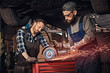 Two bearded auto mechanic in a uniform and safety glasses working with an angle grinder while standing under lifting car in repair garage.