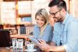 Happy young couple browsing online shop on a tablet, sitting in a cafe