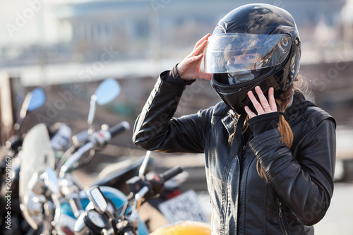Motorcyclist Caucasian woman sets her full-face helmet, portrait against bikes background, copy space