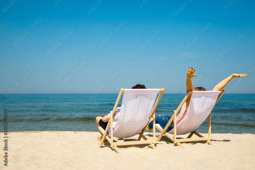 Fototapeta Woman and man relaxing on beach