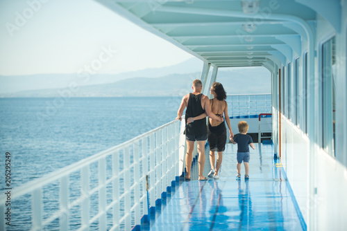 family with son walking on cruise liner deck, full body. Fototapeta