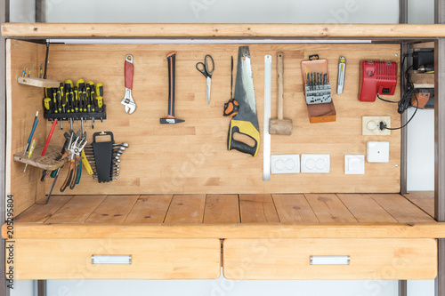 Obraz Wooden workbench at workshop. Lot of different tools for diy and repair works. Wood desk for product placement. Copyspace. Labour day - fototapety do salonu