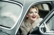 Sexy woman in fur coat sitting in retro car.