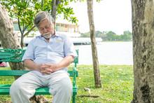 Senior Man Sleeping On A Park Bench. Chinese Old Man, Medium Shot.