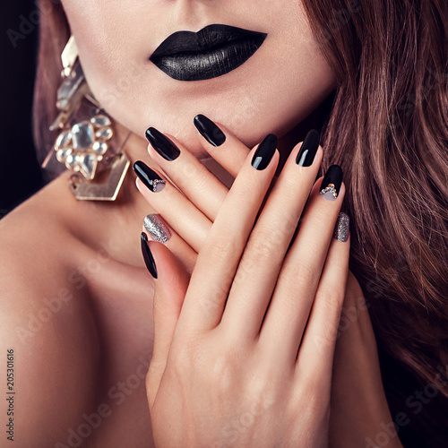 Staande foto Manicure Fashion model with dark make-up, long hair and black and silver trendy manicure wearing jewellery. Black lipstick