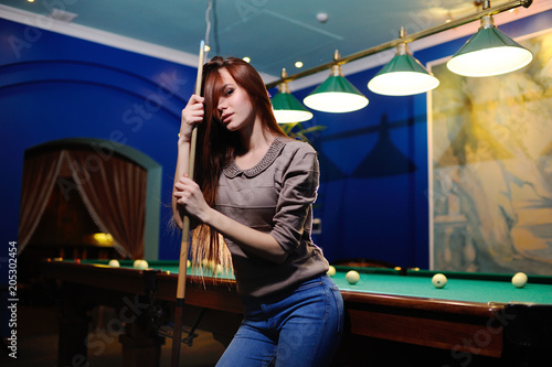 Fotografía nice cute girl with a cue in her hands playing billiards