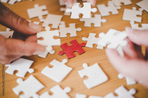 Fototapety, obrazy: Three hands hold puzzles on wood table, Team work concept