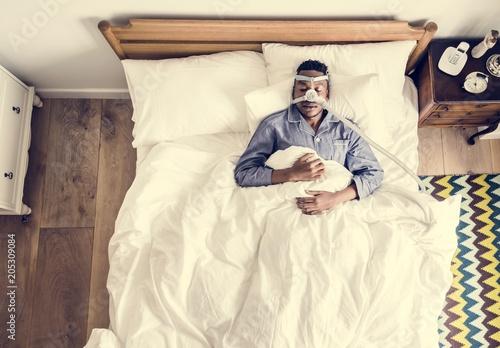 Man sleeping with an anti-snoring mask Wallpaper Mural