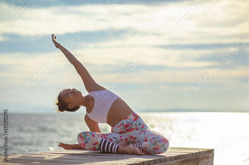 Staande foto School de yoga younger woman playing yoga pose on sea pier