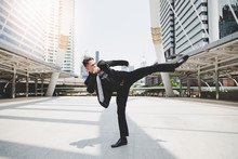 Handsome Businessman Get Angry His Boss And Wants To Relieve Stress And Furious. Cool Guy Is Exercising By Kicking On The Air. Attractive Man Wears Suit, Necktie, Long Trousers. Cityscape Background