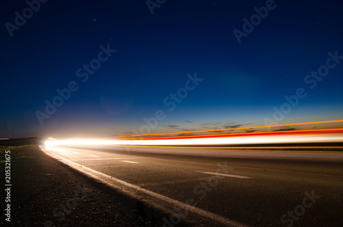Fotografering  The asphalt road in the countryside with the light passing through it at the spe