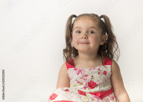 Obraz na płótnie Cute, little girl toddler with expression of mischief  on her face, isolated on