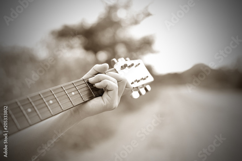 Close-up male hand playing on acoustic guitar outdoor with sunlight Canvas-taulu
