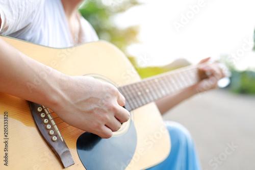 Carta da parati Male playing acoustic guitar in the nature.