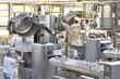 Arbeiter bedient Knetmaschinen in einer Großbäckerei - industrielle Herstellung am Fliessband von Brot in der Lebensmittelindustrie // kneading machines in a large bakery - food industry