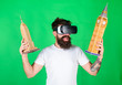 canvas print picture - Hipster on happy face study architecture in virtual reality. Guy in VR glasses hold in hands Big Ben and Empire State Building. Man with beard in VR glasses, green background. VR education concept
