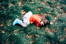 Girl Lying Down On Grass And Fall Leaves