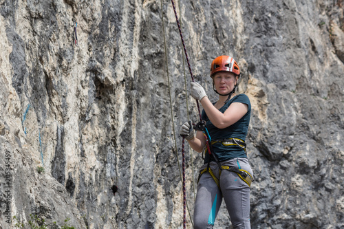 Foto op Plexiglas Alpinisme A woman climber in full gear (helmet, safety system etc) is insured by a climber standing near a rock route