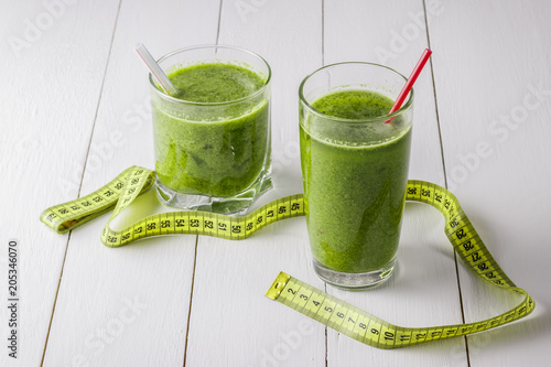 Photo  Green vegetable smoothie on a white wooden table.