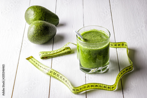 Green vegetable smoothie on a white wooden table. Canvas Print