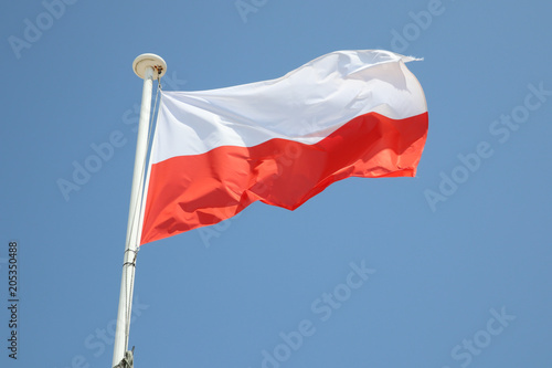 Obraz poland flag on a mat in the wind and blue sky - fototapety do salonu