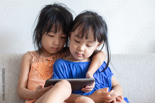 Asian Chinese little sisters using tablet on the sofa Canvas Print