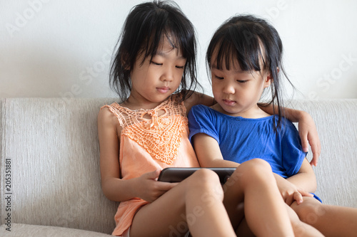 Photo Asian Chinese little sisters using tablet on the sofa