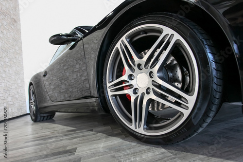 Tablou Canvas Black sport car on showroom floor with shiny wheel