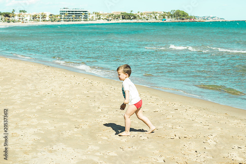 Little boy walking along the beach