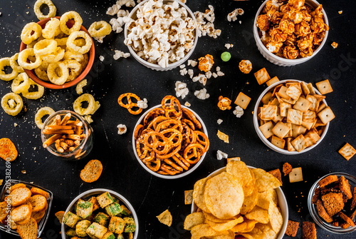 Variation different unhealthy snacks crackers, sweet salted popcorn, tortillas, nuts, straws, bretsels, back chalkboard copy space