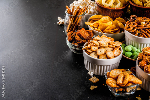 Photo Variation different unhealthy snacks crackers, sweet salted popcorn, tortillas,