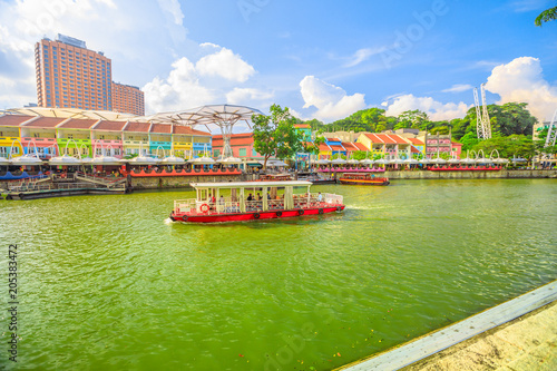 Turistic boat on Singapore River at Clarke Quay and Riverside area on a sunny day with blue sky. Singapore, Southeast Asia.