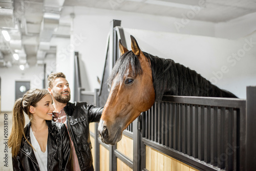 Fotografía Young couple riders in leather jackets standing with horse in the beautiful stab