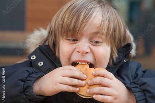 Fotografie, Obraz  Little boy (5-6) eating hamburger