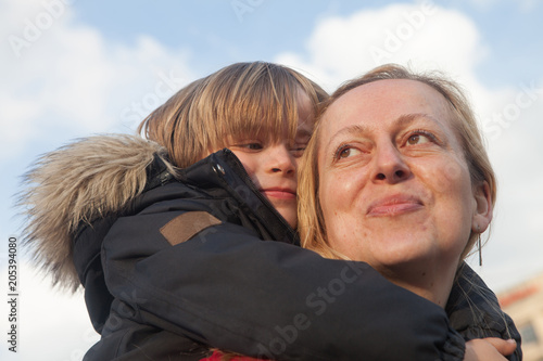 Fotografie, Obraz  Happy and proud mother carries her little son in the back