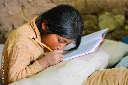 Fotografía  Poor native american girl doing her hometask.