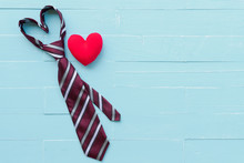 Happy Fathers Day Concept. Red Tie In Heart Shape And Handmade Red Heart On Bright Blue Pastel Wooden Table Background.