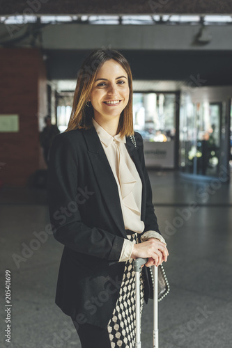 Portrait of smiling young business woman at train station with a handbag and suitcase