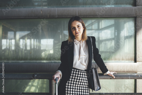 Portrait of confident young business woman waiting at airport terminal with suitcase and a handbag