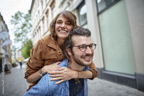 Young man carrying girlfriend piggyback in the city